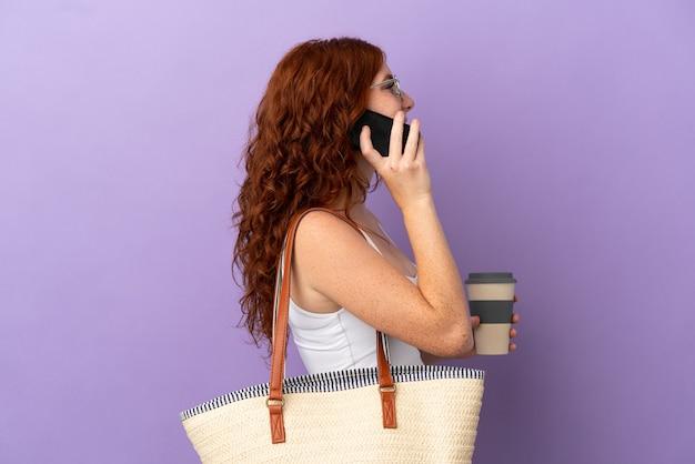 Nastolatka ruda dziewczyna trzyma torbę plażową na białym tle na fioletowym tle, trzymając kawę na wynos i telefon komórkowy