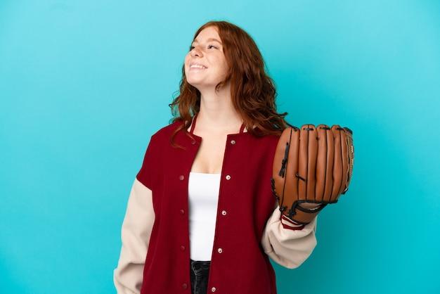Nastolatka ruda dziewczyna z rękawicą baseballową na białym tle na niebieskim tle myśląca o pomyśle, patrząc w górę
