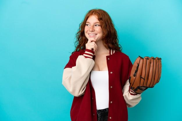 Nastolatka ruda dziewczyna z rękawicą baseballową na białym tle na niebieskim tle, patrząc w bok i uśmiechnięta