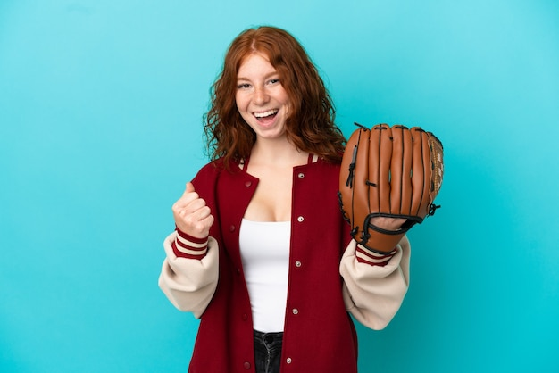 Nastolatka ruda dziewczyna z rękawicą baseballową na białym tle na niebieskim tle świętuje zwycięstwo w pozycji zwycięzcy