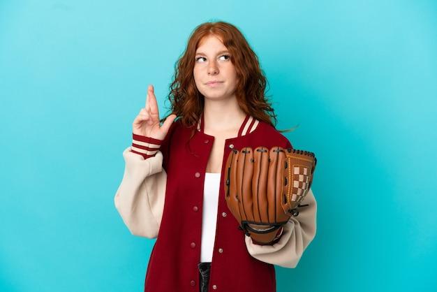 Nastolatka ruda dziewczyna z rękawicą baseballową na białym tle na niebieskim tle z palcami skrzyżowanymi i życzącymi wszystkiego najlepszego