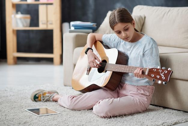 Nastolatka-samouk, siedząca na dywanie i grająca na gitarze przy użyciu filmu instruktażowego na tablecie