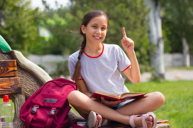 Nastolatka siedząca na ławce w parku pokazuje kciuk w górę i trzyma książkę na kolanach powrót do koncepcji szkoły