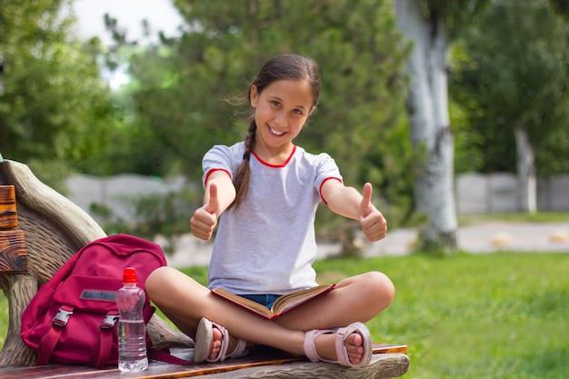 Nastolatka siedzi na ławce w parku szczęśliwie pokazuje fajnie trzyma książkę na kolanach powrót do koncepcji szkoły