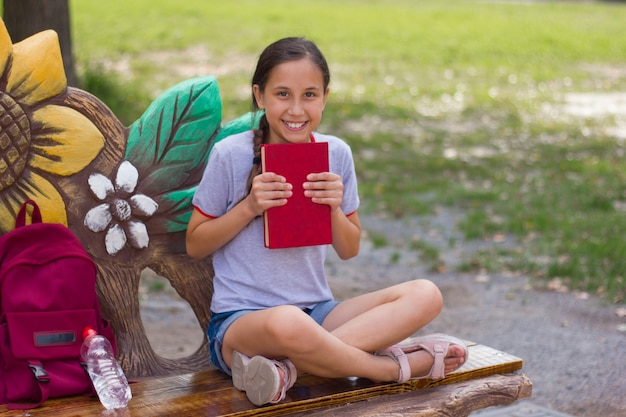 Nastolatka siedzi na ławce w parku, szczęśliwie trzymając przed sobą książkę powrót do koncepcji szkoły