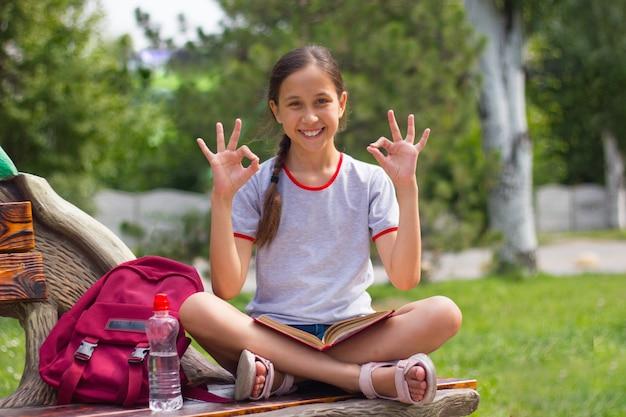 Nastolatka siedzi na ławce w parku z książką patrząc w kamerę i pokazuje palce ok