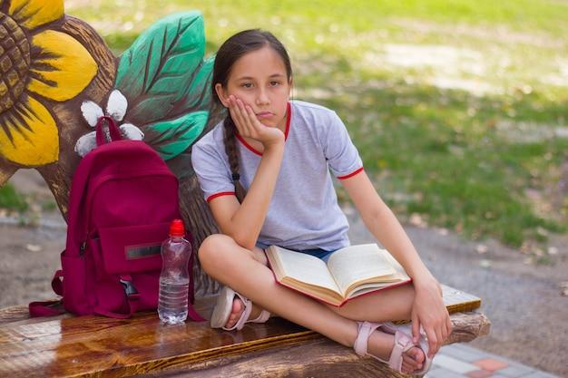 Nastolatka siedzi na ławce w parku zamyślona, trzymając książkę na kolanach powrót do koncepcji szkoły