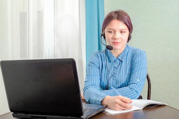 Nastolatka siedzi przed laptopem ze słuchawkami i pisze coś w swoim notesie podczas zajęć online.
