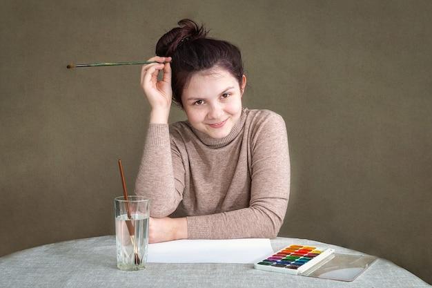Nastolatka siedzi przy biurku w domu, myśląc o tym, co zamierza namalować.