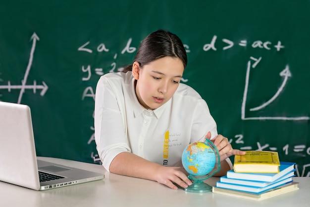 Nastolatka siedzi przy stole i patrzy na koncepcję uczenia się online w świecie