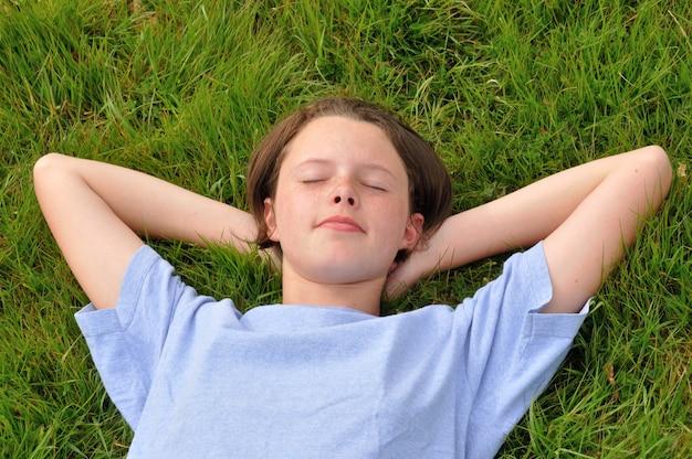Nastolatka śpi na trawniku