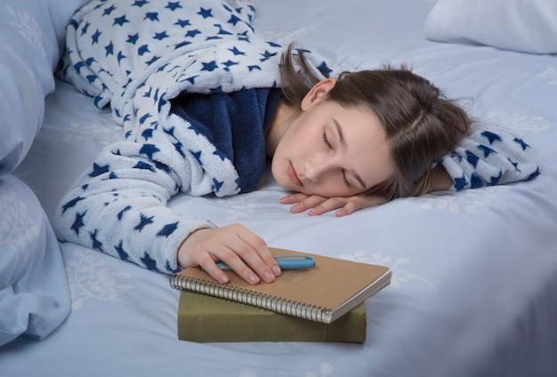 Nastolatka śpi w nocy na książkach.