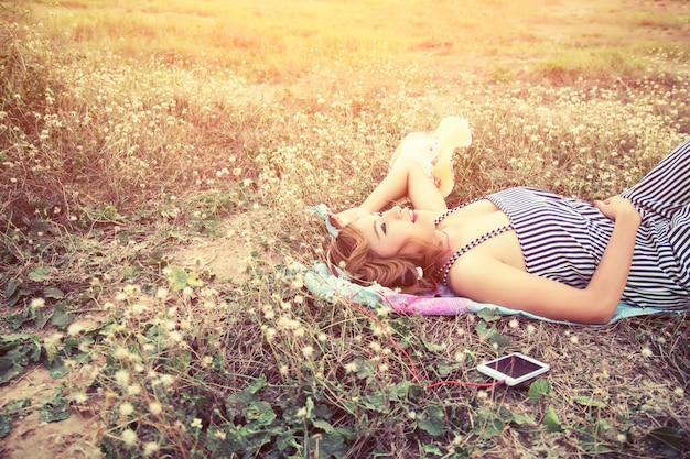 Nastolatka spoczywa na zachodzie słońca