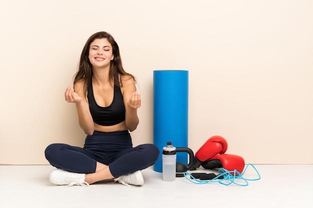 Nastolatka sport dziewczyna siedzi na podłodze, robiąc gest pieniędzy