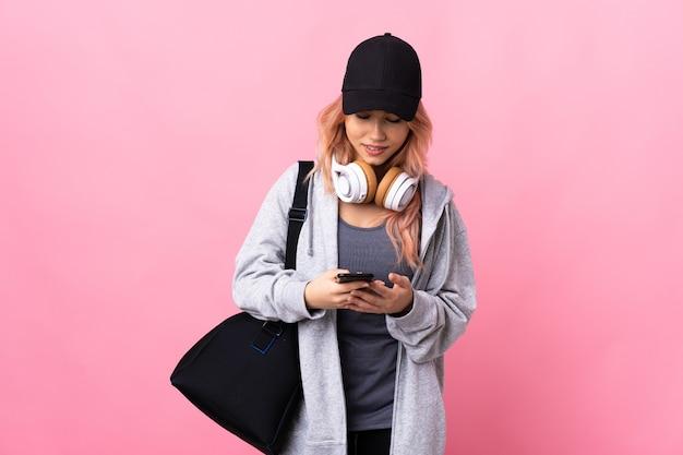 Nastolatka sportowa kobieta z torbą sportową na odizolowanej ścianie, wysyłając wiadomość za pomocą telefonu komórkowego