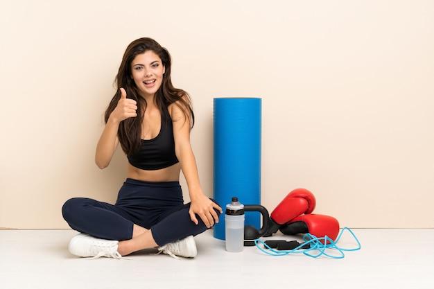 Nastolatka sportu dziewczyna siedzi na podłodze z kciuki do góry, ponieważ stało się coś dobrego