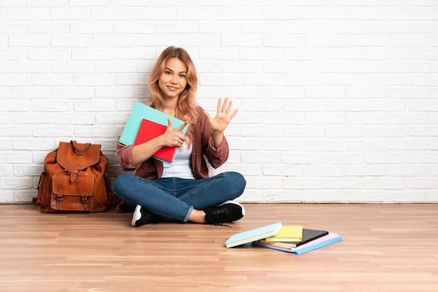 Nastolatka studentka z różowymi włosami siedzi na podłodze w pomieszczeniu licząc siedem palcami