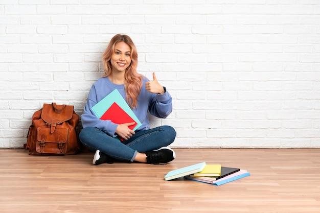 Nastolatka studentka z różowymi włosami siedzi na podłodze w pomieszczeniu, pokazując znak ok i kciuk w górę gest