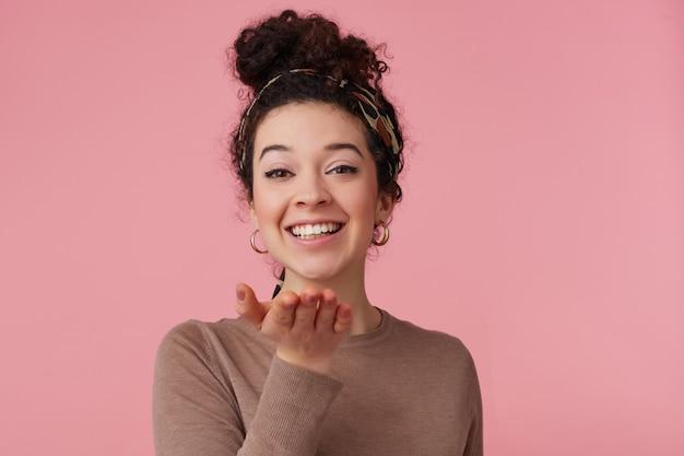 Nastolatka, szczęśliwa kobieta patrząc z ciemnymi kręconymi włosami kok. nosi opaskę, kolczyki i brązowy sweter. uzupełniał. uśmiechnięty nad dłonią