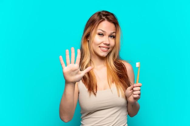 Nastolatka szczotkuje zęby na odosobnionym niebieskim tle, licząc pięć palcami