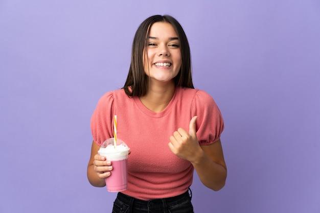Nastolatka trzyma truskawkowy koktajl mleczny, wskazując na bok, aby przedstawić produkt