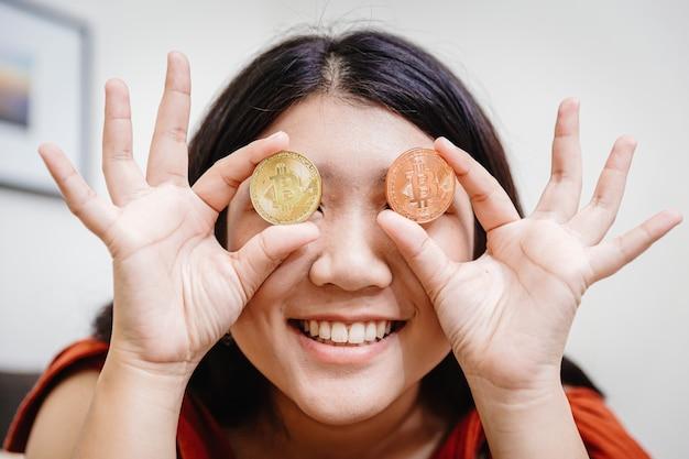 Nastolatka trzymająca bitcoina w oczach, aby zobaczyć szczęśliwie wyglądającą wizję rynku do handlu koncepcją kryptowalut