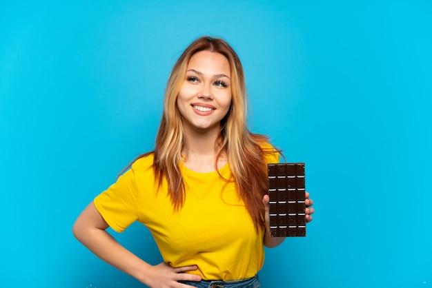 Nastolatka trzymająca czekoladę na białym tle, pozowanie z rękami na biodrach i uśmiechnięta