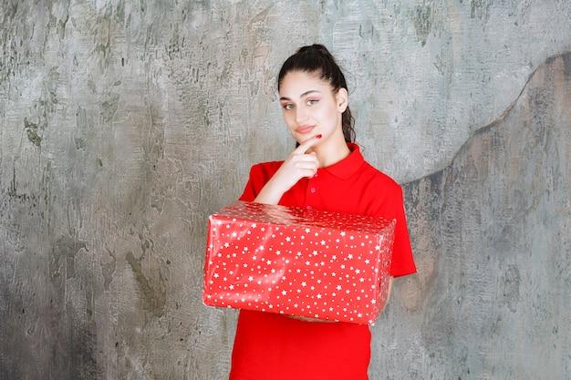 Nastolatka trzymająca czerwone pudełko z białymi kropkami i wygląda na zamyśloną