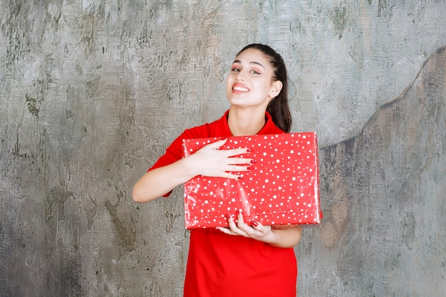 Nastolatka trzymająca czerwone pudełko z białymi kropkami