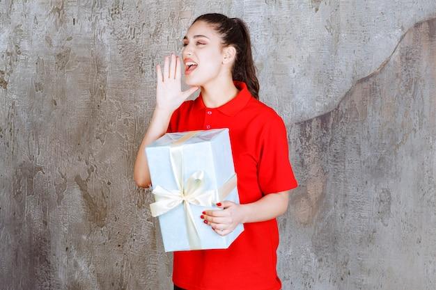 Nastolatka trzymająca niebieskie pudełko owinięte białą wstążką i dzwoniąca do kogoś