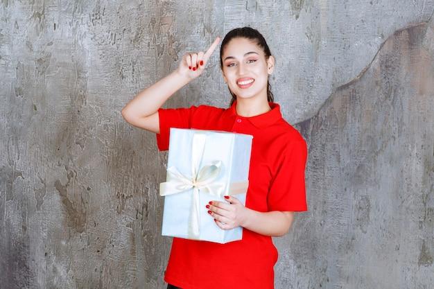 Nastolatka trzymająca niebieskie pudełko owinięte białą wstążką i marząca lub mająca dobry pomysł
