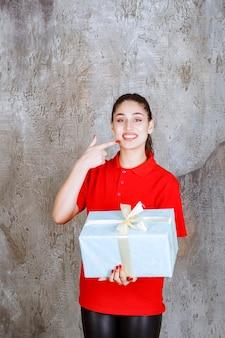 Nastolatka trzymająca niebieskie pudełko owinięte białą wstążką