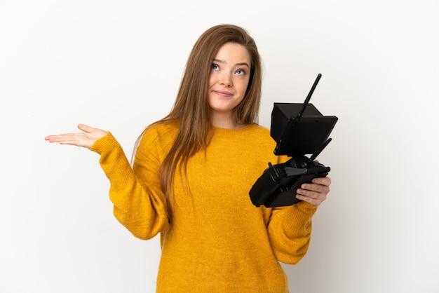 Nastolatka trzymająca pilota drona na białym tle, mająca wątpliwości podczas podnoszenia rąk