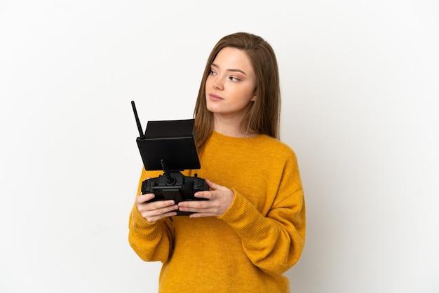 Nastolatka trzymająca pilota drona na białym tle patrząc w bok