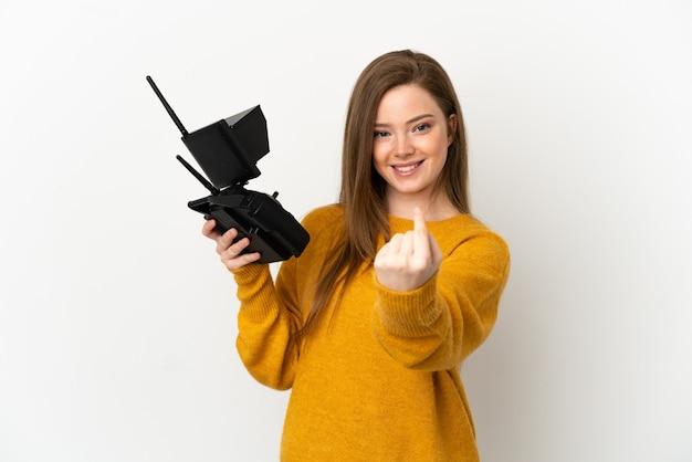 Nastolatka trzymająca pilota drona na białym tle, wykonująca gest nadchodzący