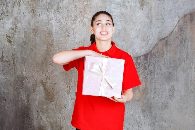 Nastolatka trzymająca różowe pudełko owinięte białą wstążką i wygląda na zamyśloną