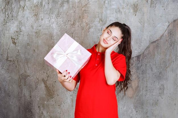 Nastolatka trzymająca różowe pudełko owinięte białą wstążką i wygląda na zmęczoną i senną