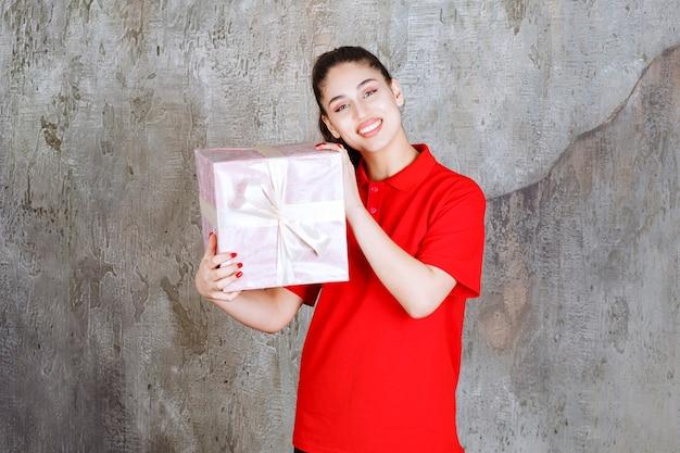 Nastolatka trzymająca różowe pudełko owinięte białą wstążką