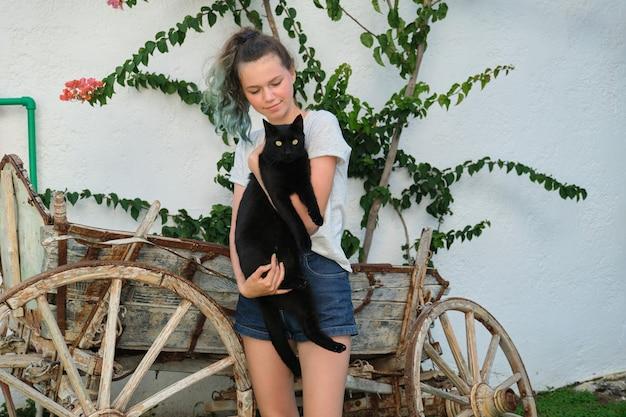 Nastolatka trzymająca w ramionach dużego czarnego kota, odkryty, słoneczny letni dzień