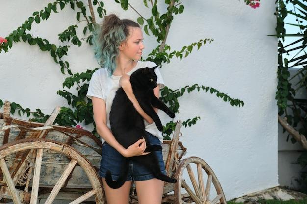 Nastolatka trzymająca w ramionach wielkiego czarnego kota, odkryty, słoneczny letni dzień