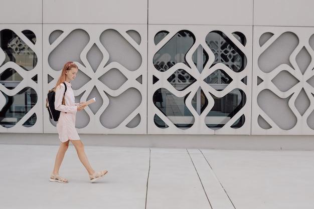 Nastolatka uczennica na tle betonowego budynku z plecakiem na plecach, kopia przestrzeń