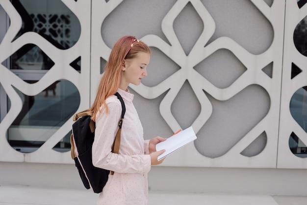 Nastolatka uczennica na tle betonowego budynku z plecakiem na plecach z książką, miejsce. zdjęcie