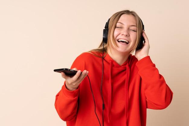 Nastolatka ukraińska kobieta na beżowej przestrzeni słuchania muzyki z telefonu komórkowego i śpiewu