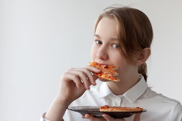 Nastolatka w białej koszuli trzyma w jednej ręce talerz pizzy, a w drugiej kawałek pizzy, który zjada.