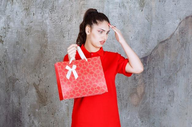 Nastolatka w czerwonej koszuli trzyma czerwoną torbę na zakupy i wygląda na zdezorientowaną i zamyśloną