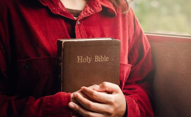Nastolatka w czerwonej koszuli trzyma w ramionach biblię