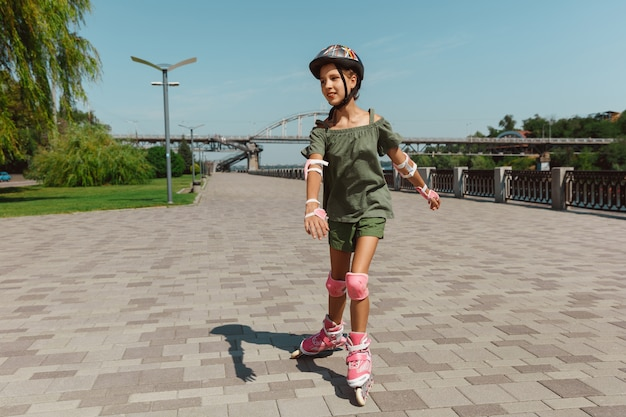 Nastolatka w kasku uczy się jeździć na rolkach na zewnątrz
