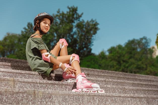 Nastolatka w kasku uczy się jeździć na rolkach, trzymając równowagę lub jeżdżąc na rolkach i kręcić się na miejskiej ulicy w słoneczny letni dzień