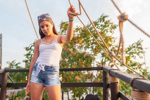 Nastolatka w krótkich spodenkach i kapeluszu stoi na otwartym balkonie stylizowanym na statek piracki l ciepły letni wieczór na tle błękitnego nieba