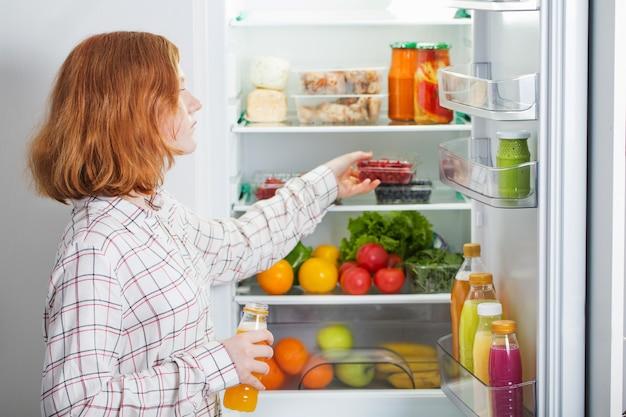 Nastolatka w lodówce z jedzeniem